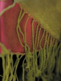 How is silk woven to produce a reversible two-tone scarf ?